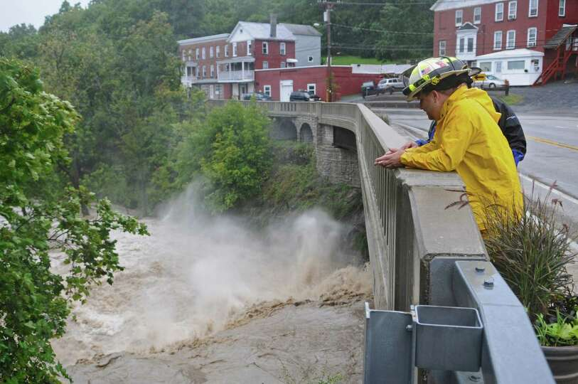 Coeymans Fire Chief Ken Dottino watches the raging Coeymans Creek from Route 144 as a result of Trop