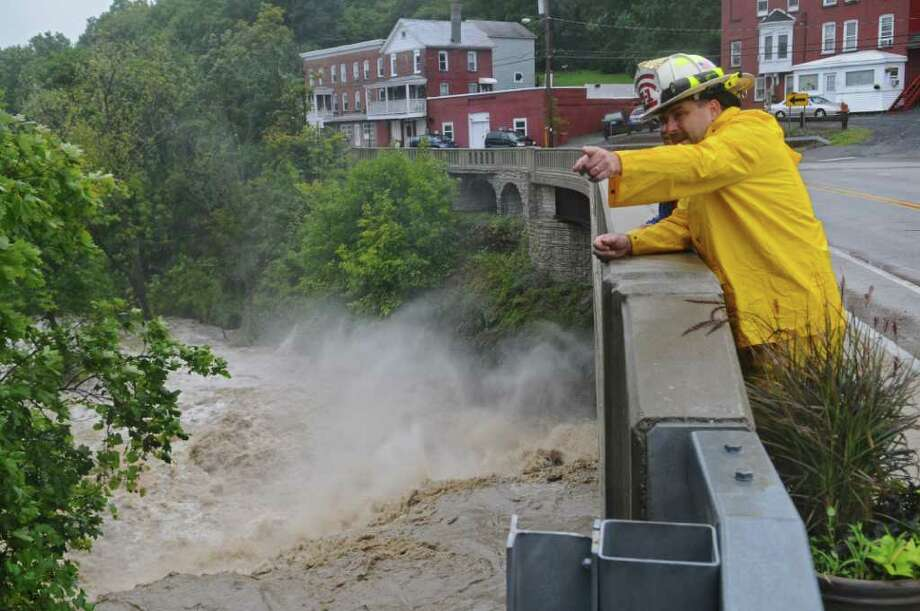 Coeymans Fire Chief Ken Dottino watches the raging Coeymans Creek from Route 144, as a result of Hurricane Irene on Sunday Aug. 28, 2011,  in Coeymans, NY.  He said they had responded to 30 calls since 8 am,  by about 4:30 pm,  at the time of the photograph. (Philip Kamrass / Times Union) Photo: Philip Kamrass