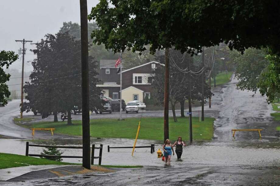 Heather Spencer, left, and Cynthia DiDominic walk on a flooded Russell Avenue as a result of Hurricane Irene on Sunday Aug. 28, 2011,  in Ravena, NY.   They had been walking around the village to see the extent of flooding. (Philip Kamrass / Times Union) Photo: Philip Kamrass