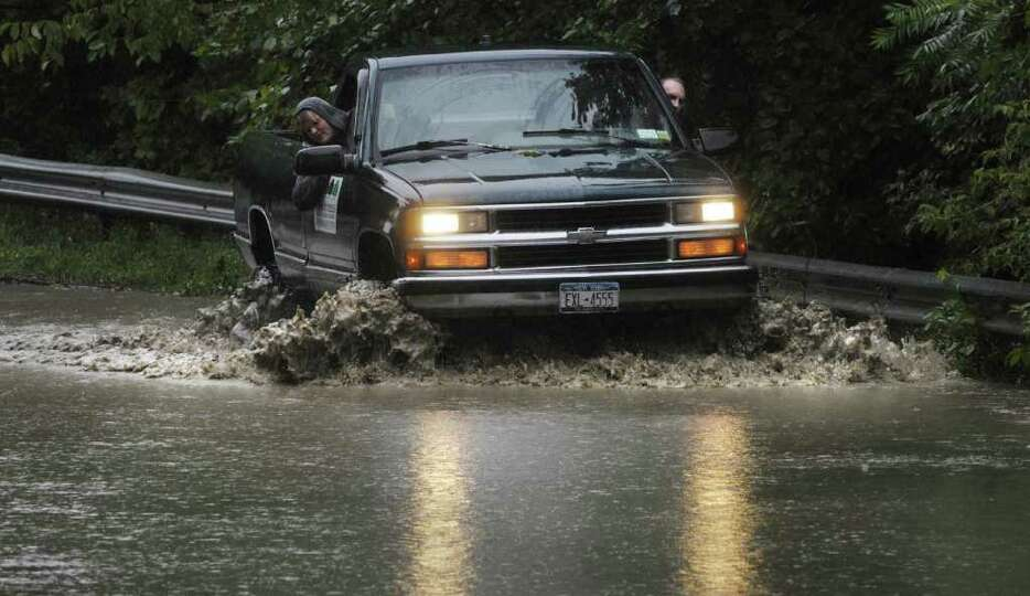 Erika Benninger, left, checks the water level from the passenger side as Jonny Haley drives his truc