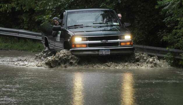 Erika Benninger, left, checks the water level from the passenger side as Jonny Haley drives his truck over a flooded section of Sunnyside Rd. in Schoharie as Irene hit the area on Sunday, Aug. 28, 2011.  Haley was going to his home to get his kitten out, and said that he knows the road so well he was confident his truck could make it through the water.  (Paul Buckowski / Times Union) Photo: Paul Buckowski, Albany Times Union / 00014427A