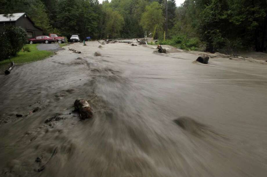 A section of Ecker Hollow Rd. becomes a river as a creek that normally runs under the road overflowed its banks as Irene hit the area on Sunday, Aug. 28, 2011 in Middleburgh.  (Paul Buckowski / Times Union) Photo: Paul Buckowski, Albany Times Union / 00014427A