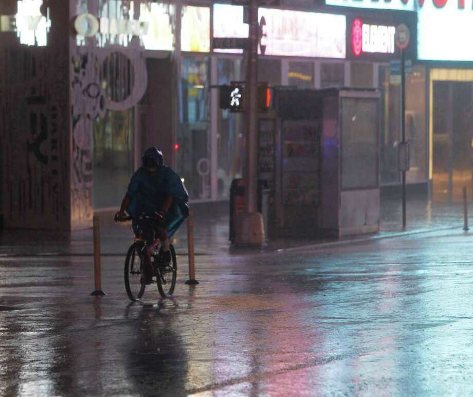 A man rides a bike in Times Square during Hurricane Irene in New York, on Sunday, Aug. 28, 2011. Barely a hurricane but massive and packed with rain, Irene lumbered onto the New Jersey shore Sunday morning on its way toward pummeling New York, which turned eerily quiet as the city hunkered down.  (AP Photo/Mike Groll) Photo: Mike Groll, STF / AP