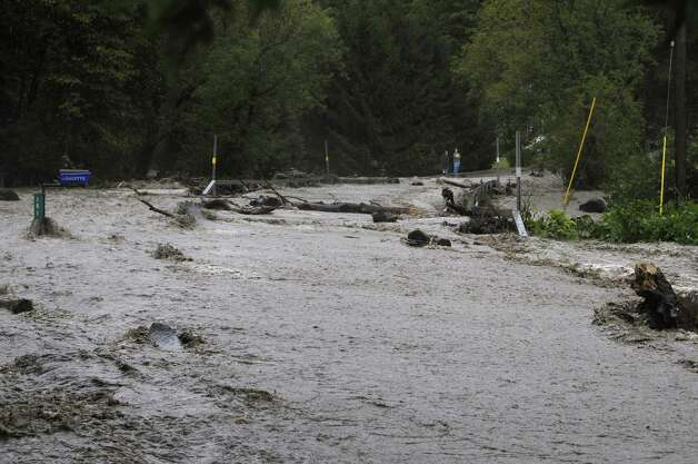 A section of Ecker Hollow Road becomes a river as a creek that normally runs under the road overflowed its banks as Irene hit the area on Sunday, Aug. 28, 2011 in Middleburgh.  (Paul Buckowski / Times Union) Photo: Paul Buckowski / 00014427A