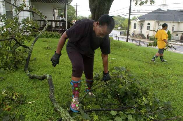 Mary Harrison, left, and her daughter, Blondell Harrison, pick up debris from Hurricane Irene in their front yard along New Street in Danbury on Sunday, Aug. 28, 2011. Photo: Jason Rearick / The News-Times