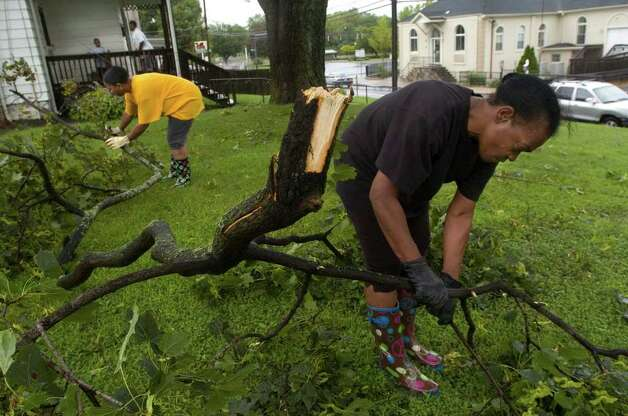 Mary Harrison, right, and her daughter, Blondell Harrison, pick up debris in their front yard along New Street in Danbury due to Hurricane Irene on Sunday, Aug. 28, 2011. Photo: Jason Rearick / The News-Times