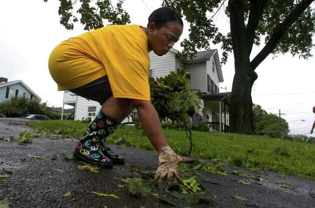Blondell Harrison picks up debris from Hurricane Irene in her front yard along New Street in Danbury on Sunday, Aug. 28, 2011. Photo: Jason Rearick / The News-Times