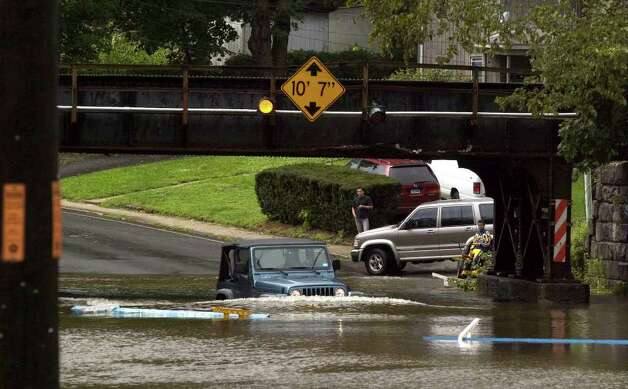 A vehicle successfully attempts to drive through the rushing water along West Street in Danbury due to Hurricane Irene on Sunday, Aug. 28, 2011. Photo: Jason Rearick / The News-Times