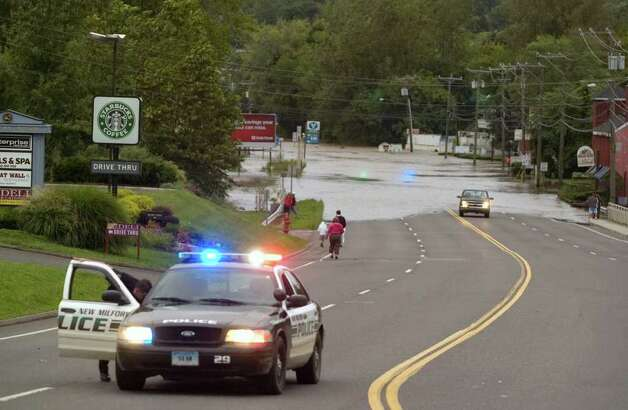 A New Milford polilce car is parked on Route 7 southbound while curious residents head down to see where the Housatonic River is spilling onto the road in New Milford on Sunday, Aug. 28, 2011. Photo: Jason Rearick