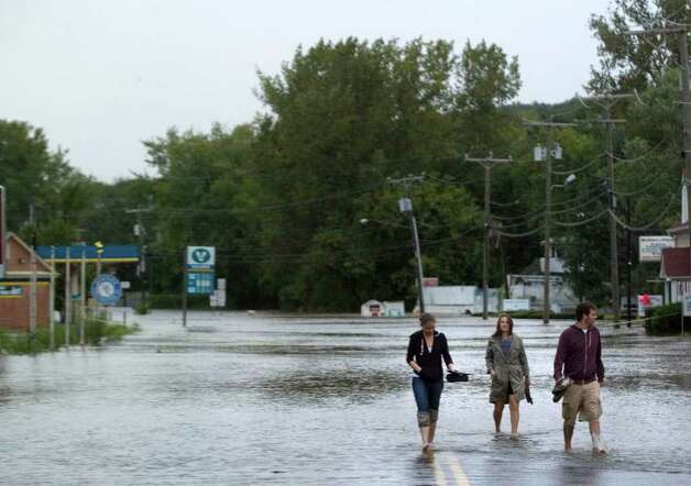 From left, Susan Anzalone, Heather Stone and Dale Mitchell, wade into the Housatonic River as it flows over Route 7 in New Milford on Sunday, Aug. 28, 2011.  Anzalone is the general manager of The Cookhouse restaurant, which was affected by the floodwater. Photo: Jason Rearick