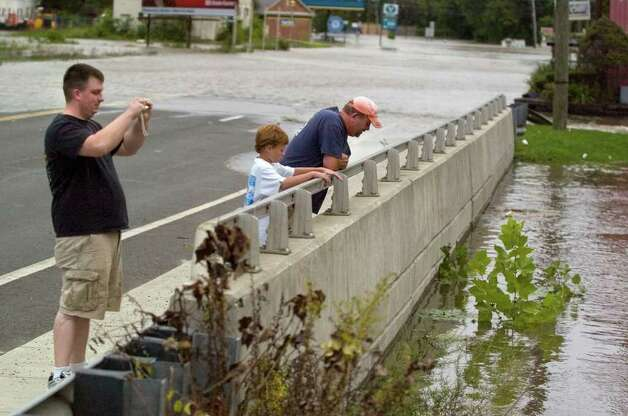 Cody Wilson, 10, center, and his father, Tim Day, look at the swollen Little Brook at Route 7 in New Milford as family friend Matt Bloom, left, photographs the flooding on Sunday, Aug. 28, 2011. Photo: Jason Rearick