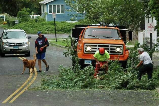 Fairfield town workers cut up downed tree limbs at the end of South Pine Creek Road in Fairfield, Conn. on Sunday Aug. 28, 2011. Lots of roads were flooded, trees and wires were down, and power was disrupted as Hurricane Irene made her way through the area. Photo: Cathy Zuraw / Connecticut Post
