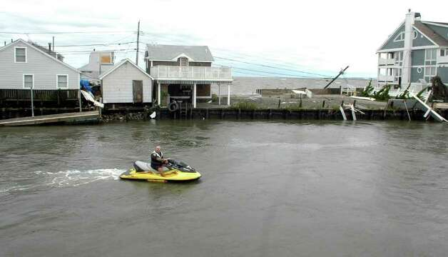 A police officer on a personal watercraft assesses the damage along Fairfield Beach Road near Pine Creek in Fairfield, Conn. as treacherous weather caused by Hurricane Irene came through the area on Sunday Aug. 28, 2011. Photo: Cathy Zuraw / Connecticut Post