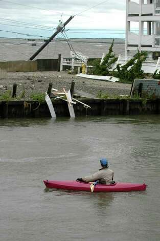 A kayaker pauses to look at the damage on Fairfield Beach Road as treacherous weather caused by Hurricane Irene came through the area on Sunday Aug. 28, 2011. Photo: Cathy Zuraw / Connecticut Post
