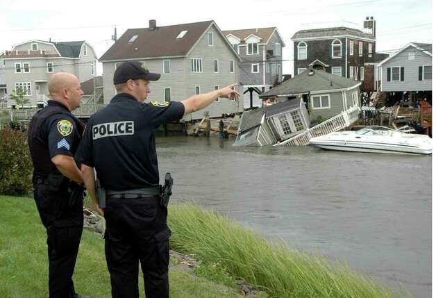 Fairfield police assess the damage along Fairfield Beach Road as treacherous weather caused by Hurricane Irene came through the area on Sunday Aug. 28, 2011. Photo: Cathy Zuraw / Connecticut Post