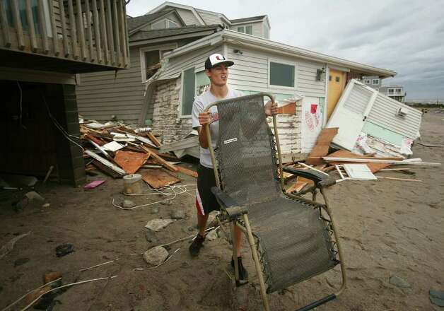 Connor McMahon salvages his aunt's chair from debris washed beneath his beachfront home by Hurricane Irene on Shoreline Drive in Stratford on Sunday, August 28, 2011. Photo: Brian A. Pounds / Connecticut Post