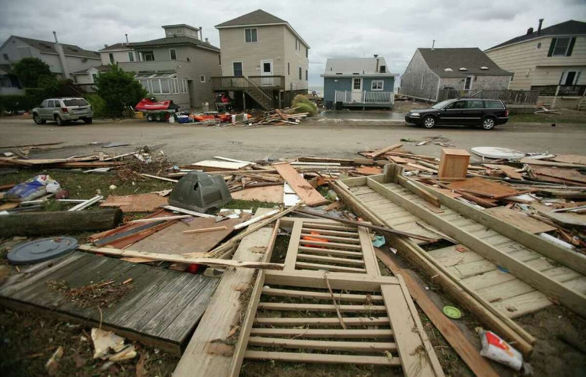 Debris from damaged dwellings is washed up well behind beachfront homes on Shoreline Drive in Stratford on Sunday, August 28, 2011.
