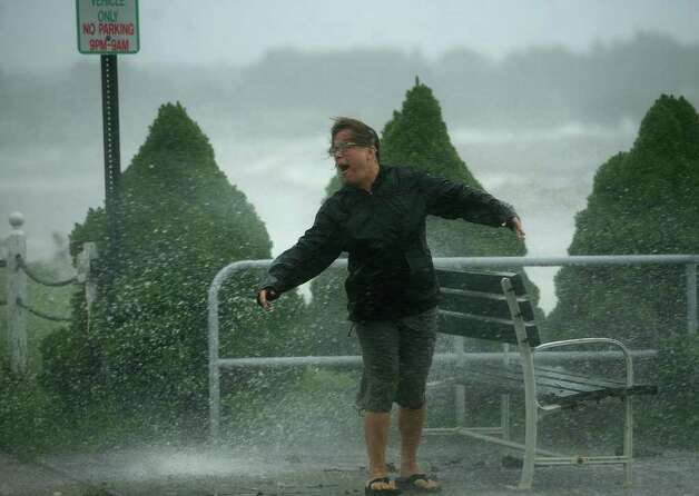 Kim Squires of Milford reacts as she is hit by a wave splashing over the seawall in the Fort Trumbull section of Milford on Sunday, August 28, 2011. Photo: Brian A. Pounds / Connecticut Post