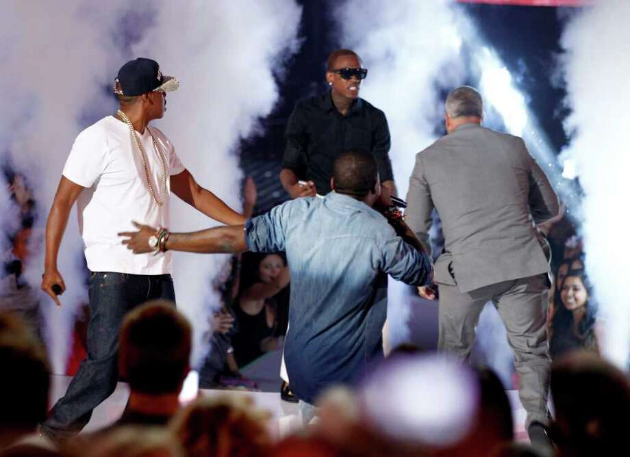 A fan dressed in black interrupts Jay-Z, left, and Kanye West's surprise performance. And a guy dressed in gray isn't too happy about it. (AP) Photo: Matt Sayles, Associated Press / AP
