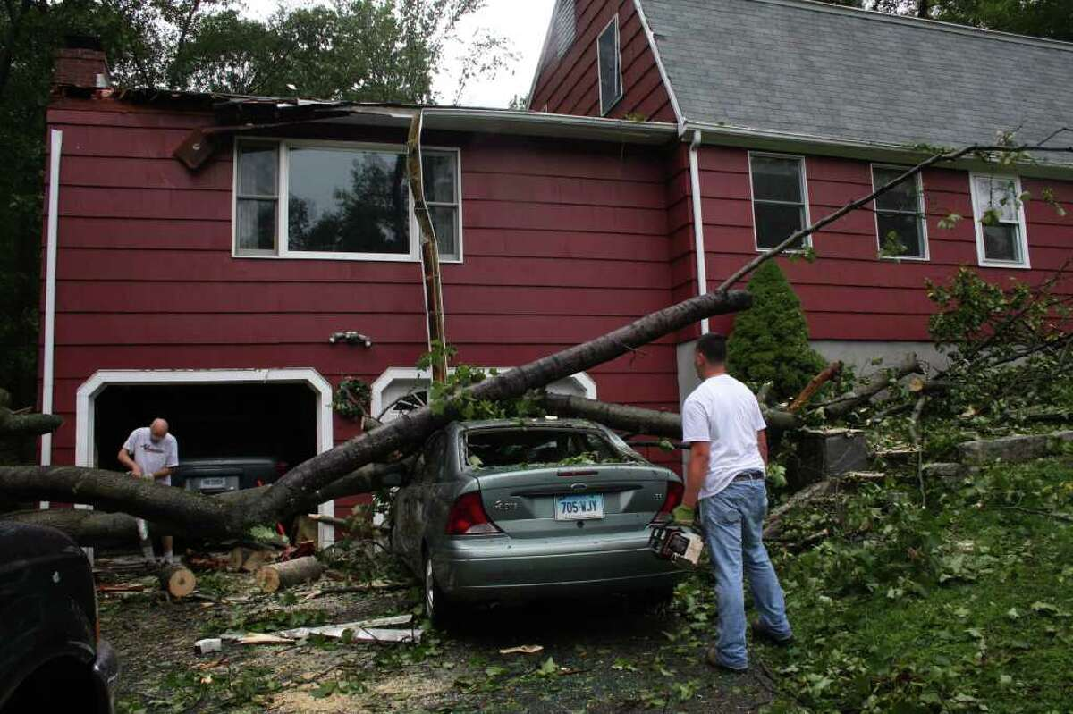 The Novitzky's examine damage to their home and car on Pasters Walk Road in Monroe after Hurricane Irene struck.