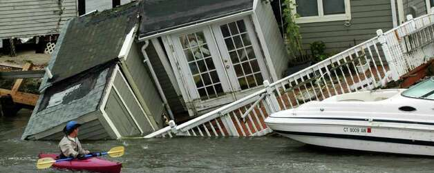 A kayaker pauses to look at a Fairfield Beach Road home that fell into Pine Creek in Fairfield, Conn. as treacherous weather caused by Hurricane Irene came through the area on Sunday Aug. 28, 2011.