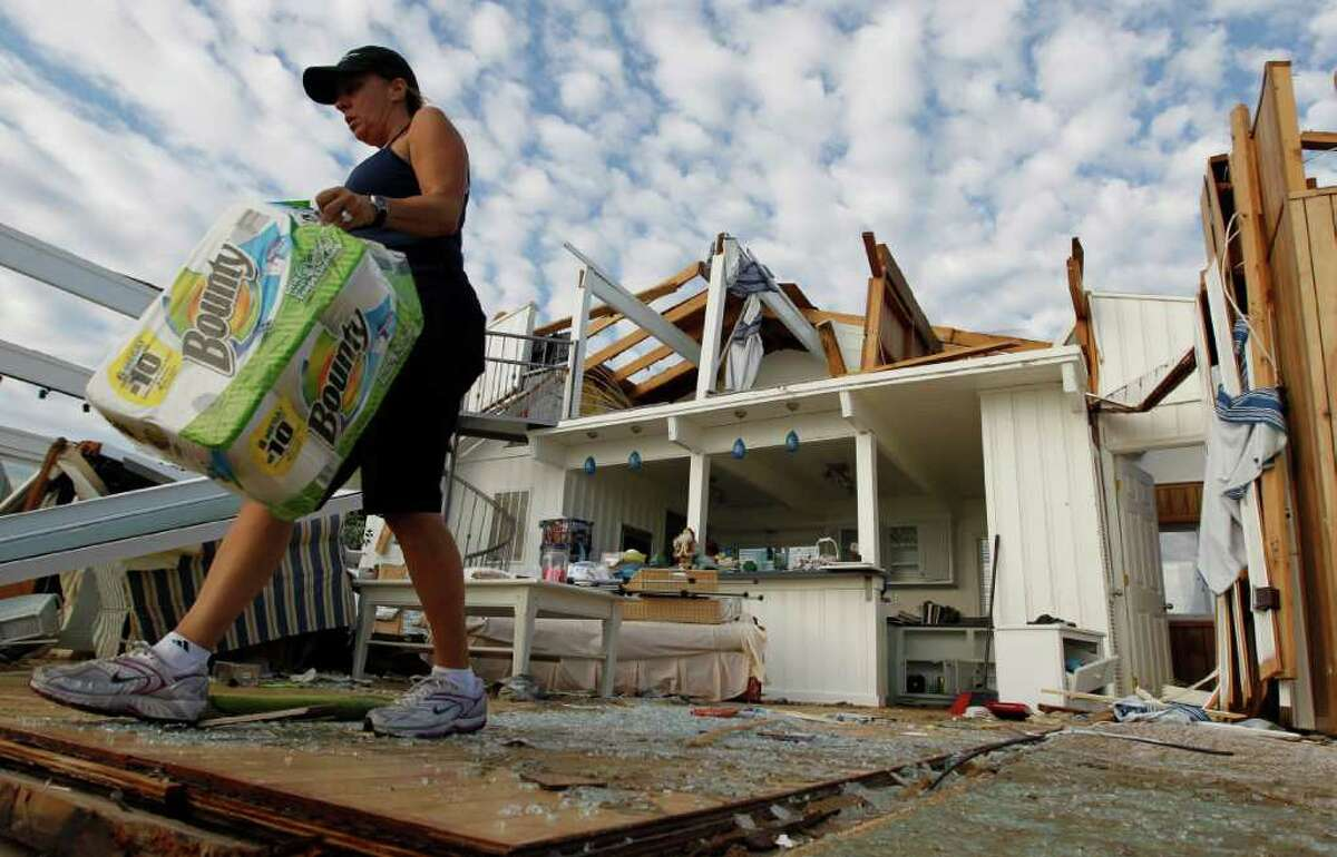 Denise Robinson clears out her destroyed beach home in the Sandbridge area of Virginia Beach after Hurricane Irene hit Virginia Beach, Va., Sunday, Aug. 28, 2011. Officials speculate that a tornado swept through the area. (AP Photo/Steve Helber)