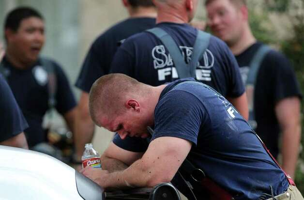 San Antonio Firefighter Coy Bartlett (foreground, center) takes a water break during the aftermath of a house fire that broke out Sunday August 28, 2011 at 7402 Tall Cedar. According to San Antonio Fire Department Battalion Chief Thomas McNulty one occupant in the home suffered minor burns and one firefighter was having his heart checked at the incident. The fire broke out about 1:50 p.m. Photo: Express-News