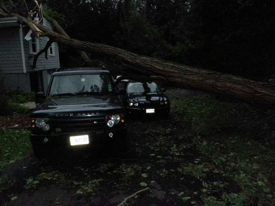 A large tree fell onto this Easton Road house and two vehicles in the driveway Sunday in the wake of Tropical Storm Irene. Photo: Westport Fire Department / Westport News contributed