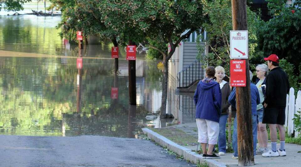 Residents of North Street in the Stockade section of Schenectady, N.Y. watch as water rises from the
