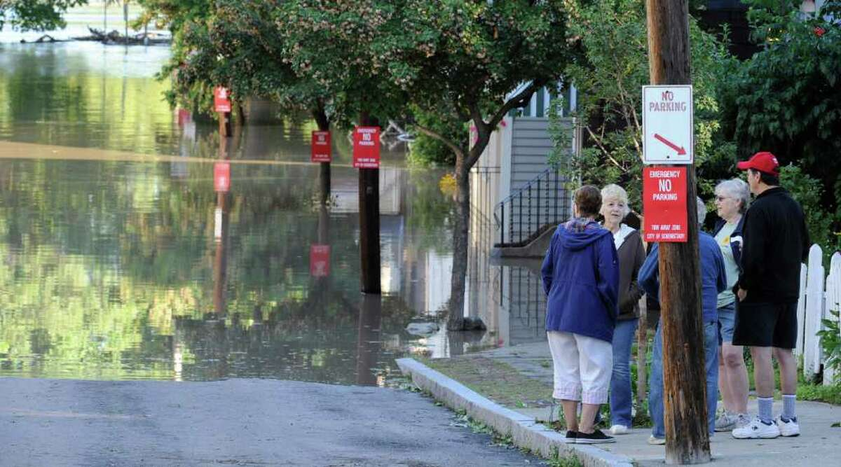 Residents of North Street in the Stockade section of Schenectady, N.Y. watch as water rises from the Mohawk River and floods homes on the street. (Skip Dickstein / Times Union)