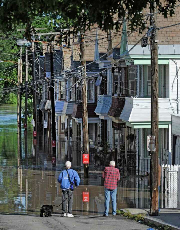 Residents of ingersoll Avenue in the Stockade section of Schenectady, N.Y. watch as water rises from the Mohawk River and floods homes on the street. (Skip Dickstein / Times Union) Photo: SKIP DICKSTEIN / 2011