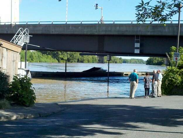 People survey the rising Hudson River Monday morning, Aug. 29, 2011, near the popular Dinosaur Bar-B-Que downtown. (Dayelin Roman / Times Union)