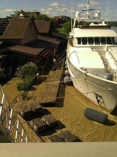 The rising Hudson River lifts a yacht outside the Dinosaur Bar-B-Que restaurant in downtown Troy. (E