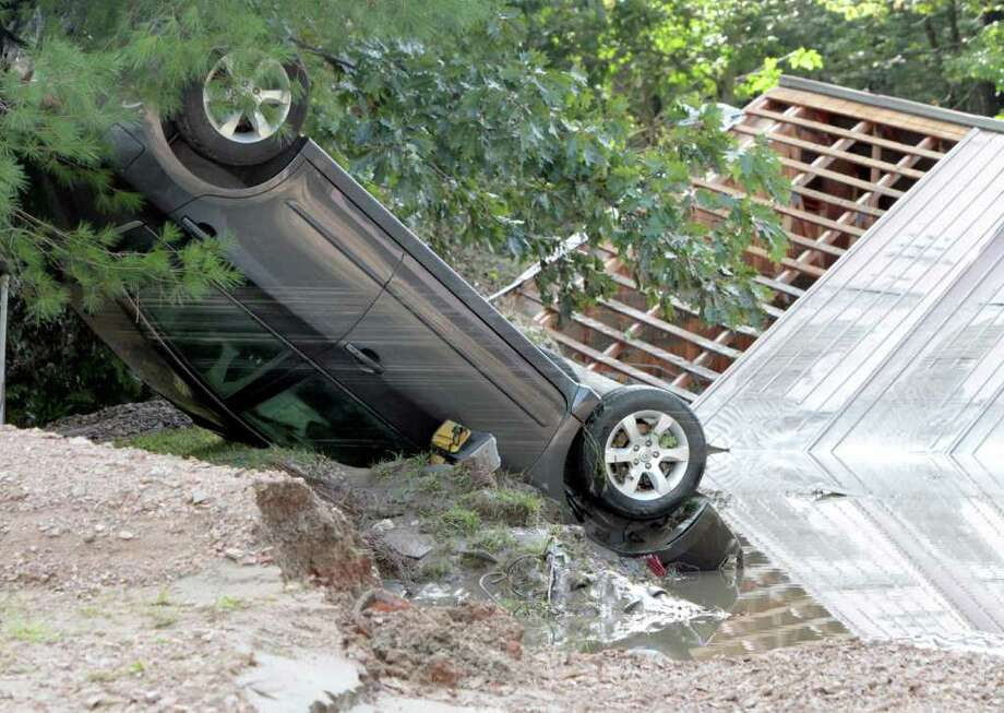 A car lies upside down in the aftermath of Tropical Storm Irene on Monday in Waterbury, Vt. Photo: AP