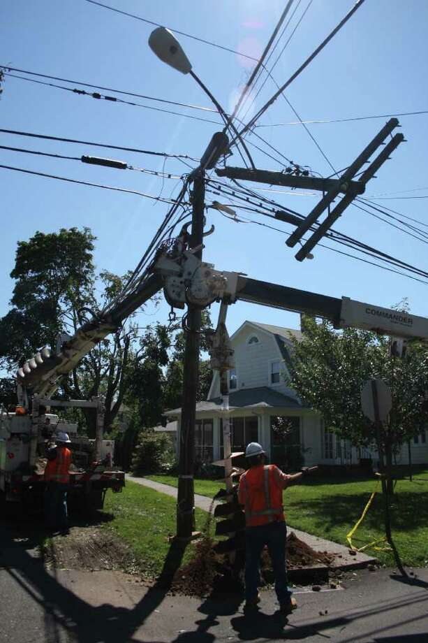 Utility crews work to repair damage from Irene on Third Avenue in Stratford Monday morning. Photo: Jeff Bustraan / Connecticut Post