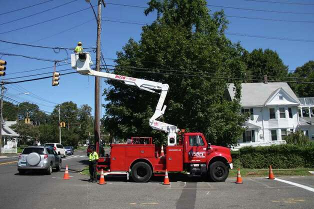 Utility crews work to repair damage from Irene on Main Street in Stratford Monday morning. Photo: Jeff Bustraan / Connecticut Post