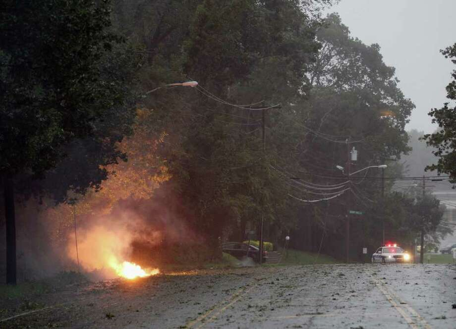 OLD BETHPAGE, NY - AUGUST 28:  A police car guards a fire that was ignited by a fallen live electric wire on Old Bethpage Road on August 28, 2011 in Old Bethpage, New York. Hurricane Irene made a second landfall in New Jersey and swept up to New York City and Long Island early this morning, battering the northeast with high winds and rain. Photo: Bruce Bennett, Getty Images / 2011 Getty Images