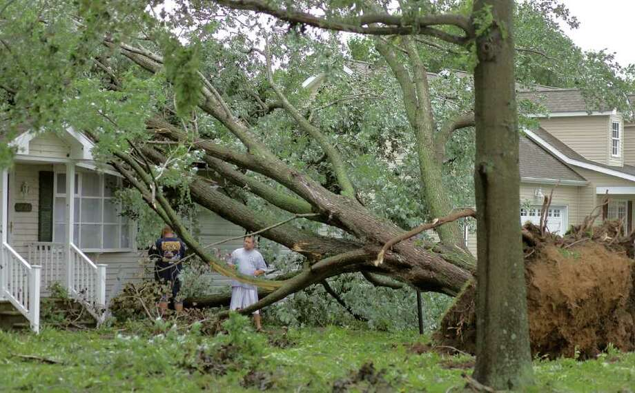 LEWES, DE - AUGUST 28: (L to R) Richard Bunting and Alex Hamilton inspect a house that a large tree fell on after a tornado spawned by Hurricane Irene touched down, on August 28, 2011 in Lewes, Delaware. During the night Hurricane Irene passed the Delaware area causing power outages, with minimal flood and wind damage. Photo: Mark Wilson, Getty Images / 2011 Getty Images