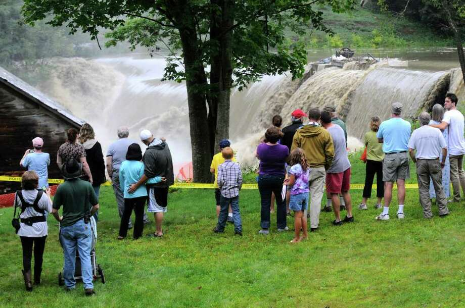 CORRECTS STATE TO VERMONT INSTEAD OF NEW HAMPSHIRE - Windsor residents watch as water rushes over the Ascutney Mill Dam on Kennedy's Pond in Windsor, Vt., Sunday, Aug. 28, 2011. A weakened but dangerous Tropical Storm Irene dumped up to half a foot of rain in places, flooded roads, knocked down trees and left more than 165,000 New Hampshire homes and businesses on the dark before blowing out of the state on Sunday. Photo: AP