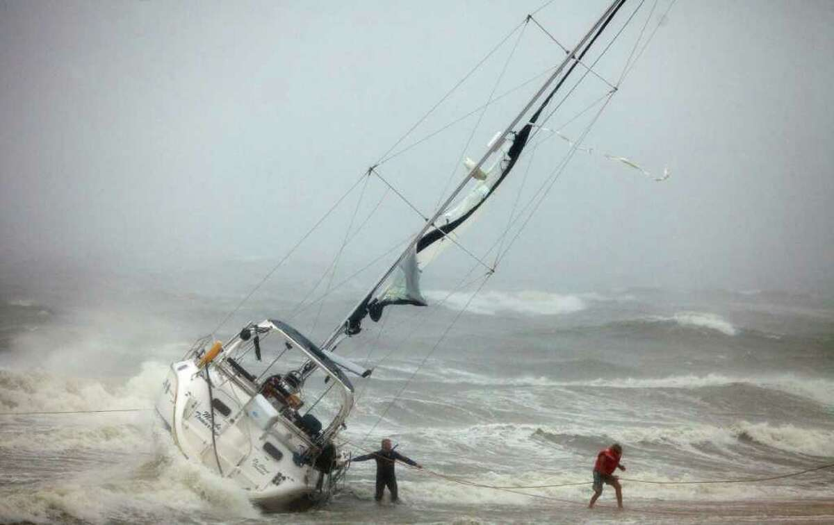 One of two people rescued from a sailboat, right, uses a line to make their way onto the beach on Willoughby Spit in Norfolk, Va., Saturday, Aug. 27, 2011, after they and another person were rescued from the boat that foundered in the waters of the Chesapeake Bay. A rescuer, left, waits for s second person to exit the boat. (AP Photo/TheVirginian-Pilot, Bill Tiernan) MAGS OUT