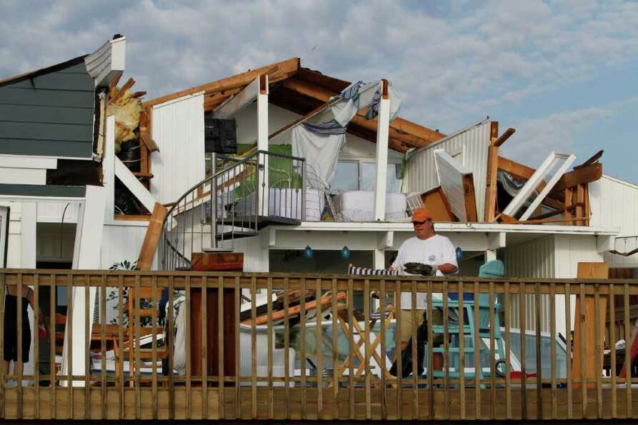 Casey Robinson clears out belongings from his severely storm-damaged beach home in the Sandbridge ar