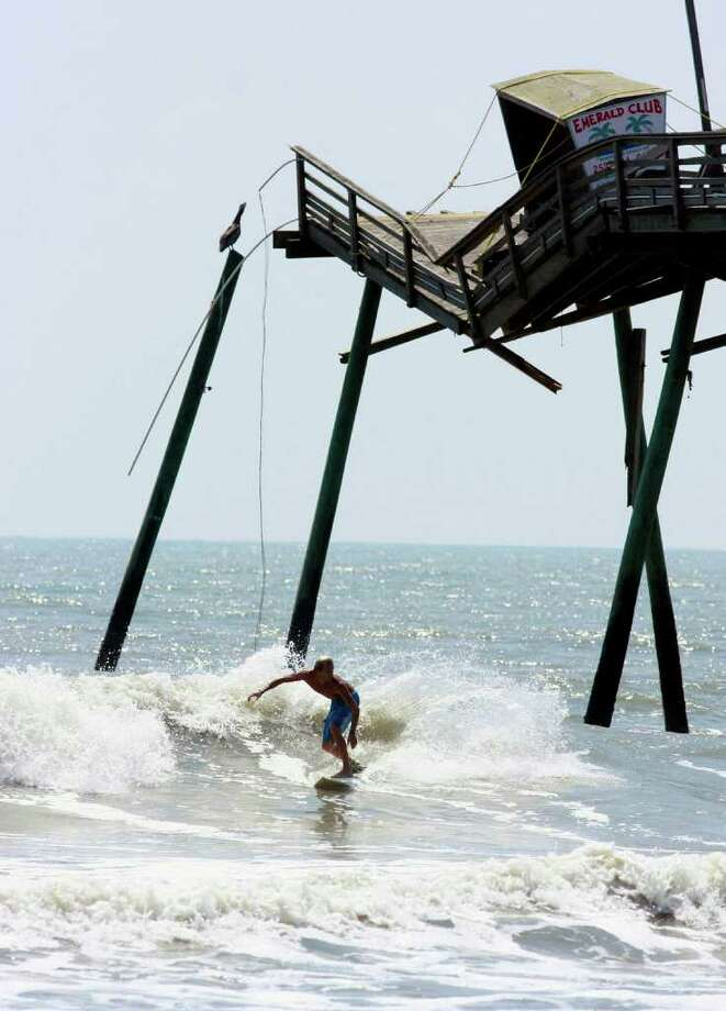 A surfer passes the broken end of the Bogue Inlet Fishing Pier in Emerald Isle, N.C. on August 28, 2011 showing the destructive power of Hurricane Irene. The storm that spent 12-hours scouring the coast killed at least five people, brought pockets of flooding that required rescues along the sounds and left nearly a half-million customers without power. (AP Photo/The News & Observer, John Rottet)  MANDATORY CREDIT Photo: AP