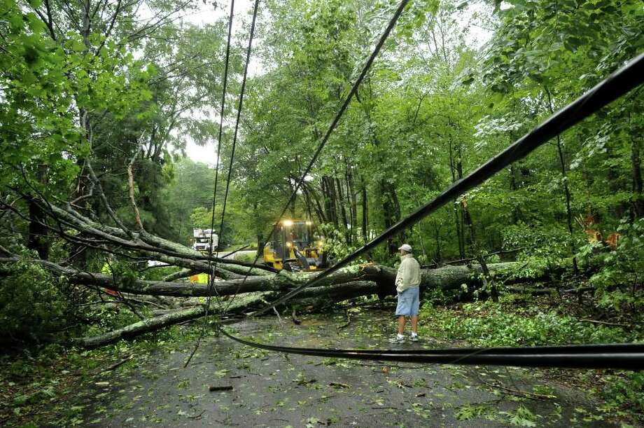 A resident of Gover Road in Millbury, Mass., watches as crews work to clear a tree downed by Tropical Storm Irene on Sunday, Aug. 28, 2011.  The winds downed trees and power lines around the state, knocking out electricity for more than half a million people. Photo: AP