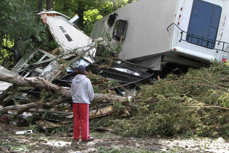 Lauren McTear looks over the remains of the trailer home owned by her boyfriend's parents on Monday, Aug. 29, 2011 in Berlin, Vt. The trailer was destroyed by a recreational vehicle which floated down the river into it. Photo: AP