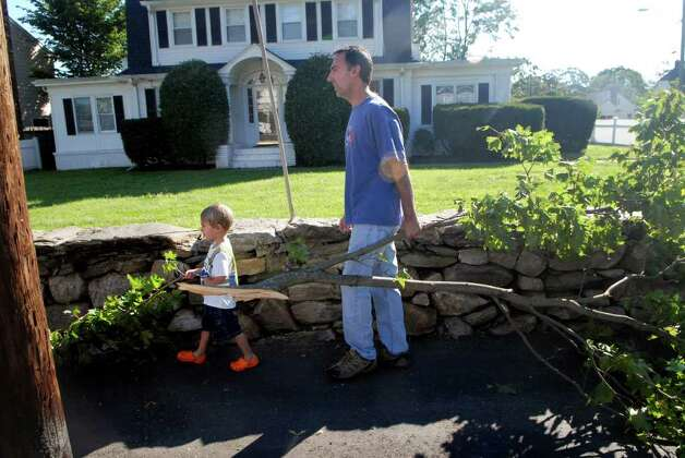 Zach Shapiro (4) helps his dad David put downed branches from their home on Shippan  Ave in Stamford, Conn. on the curb for pick up  on Monday August 29, 2011, cleaning up after tropical storm Irene. Photo: Dru Nadler / Stamford Advocate Freelance
