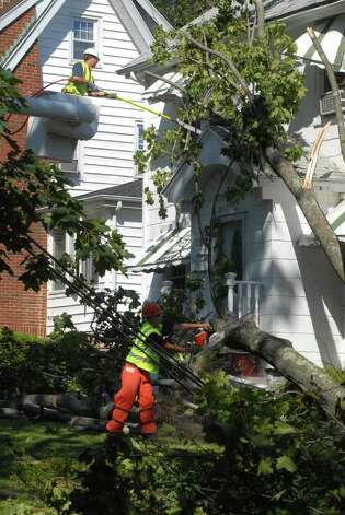 Crews work to remove a tree that fell on a home on the corner of Hamilton Ave and Field St in Stamford, Conn., cleaning up on Monday August 29, 2011 after tropical storm Irene. Photo: Dru Nadler / Stamford Advocate Freelance
