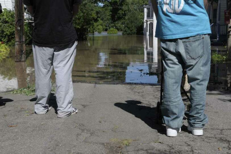 People comes to the edge of the flood waters on North Ferry St. in the Stockade section of Schenecta