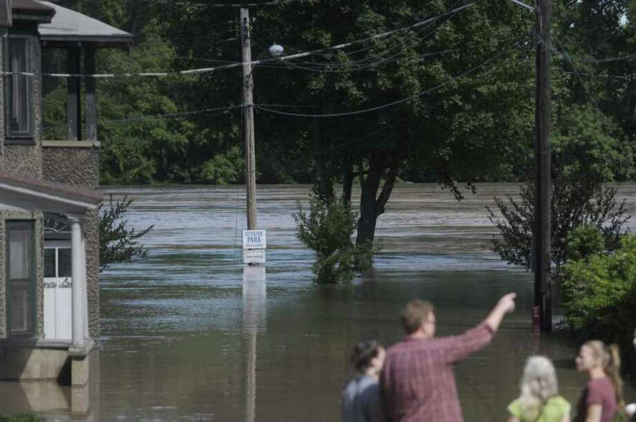 People look over the swollen Mohawk River at the end of Governor's Lane in the Stockade section of Schenectady as the Mohawk River overflowed its banks flooding homes in this section of the city on Monday, Aug. 29, 2011. (Paul Buckowski / Times Union) Photo: Paul Buckowski  / 00014438B
