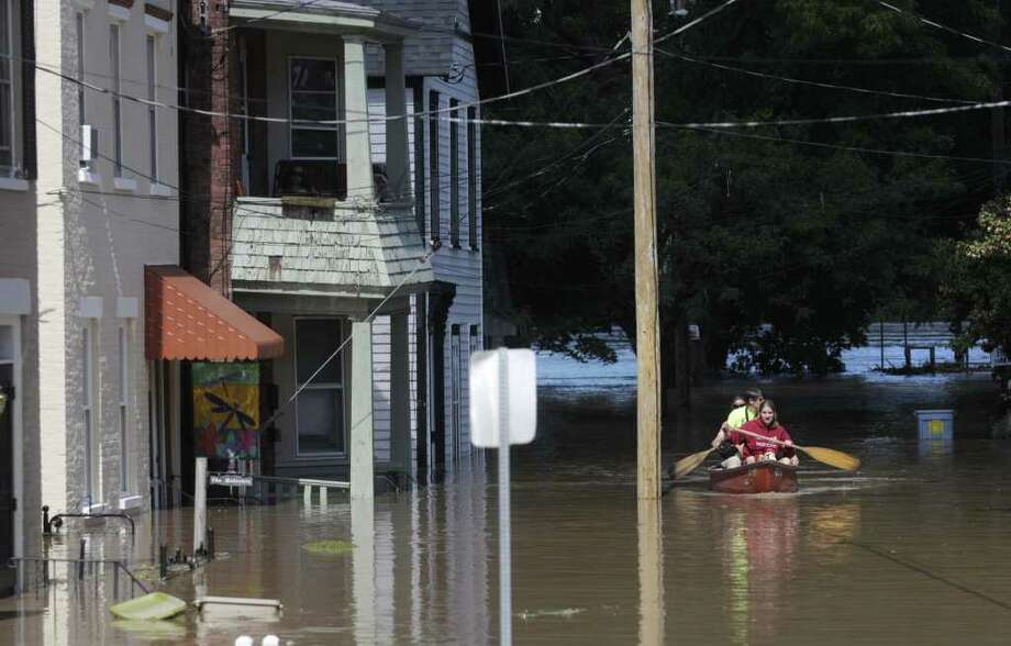 Emily Houlihan, front, 16, along with her mom Claire Houlihan, center, and Claire's sister Susan Cooley paddle a canoe up North St. in the Stockade section of Schenectady as the Mohawk River overflowed its banks flooding homes in this section of the city on Monday, Aug. 29, 2011.  Claire and Susan grew up on the street and they used the canoe to check on their parent's home.  (Paul Buckowski / Times Union) Photo: Paul Buckowski  / 00014438B