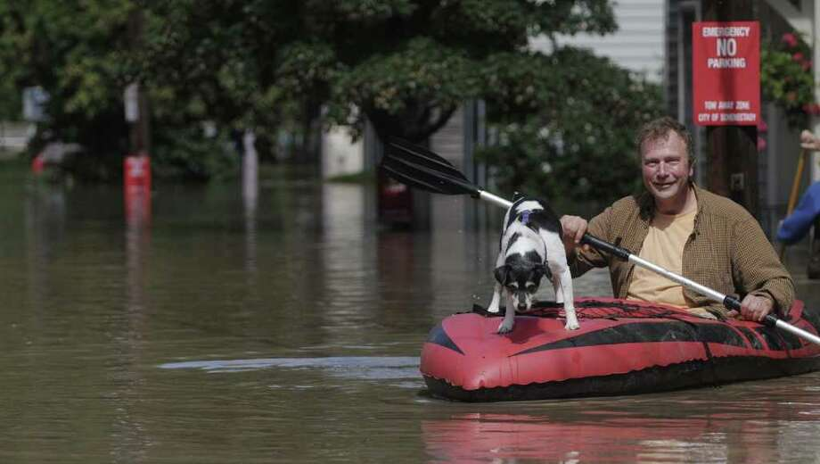 Steve Reichert and his dog Dogga, paddle out onto North St. to check his home in the Stockade section of Schenectady as the Mohawk River overflowed its banks flooding homes in this section of the city on Monday, Aug. 29, 2011. (Paul Buckowski / Times Union) Photo: Paul Buckowski  / 00014438B